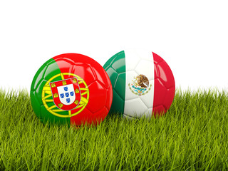 Two footballs with flags of Portugal and Mexico on green grass