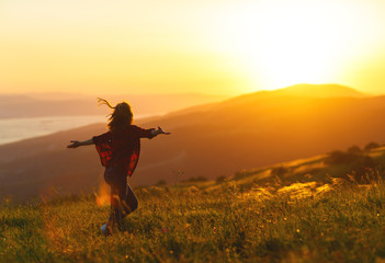 Happy woman  dances,  rejoices, laughs  on sunset in nature .