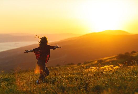 Happy woman  dances,  rejoices, laughs  on sunset in nature .
