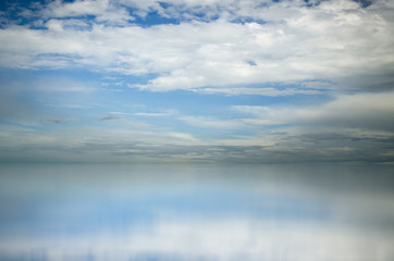 Blue sky. Dramatic clouds over sea. Blurred reflection of sky in water