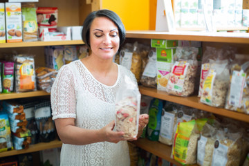 Positive mature female holding with cereal products