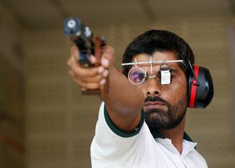 Ghulam Mustafa Bashir aims his pistol during a practice session at the Pakistan Navy Shooting Range in Karachi