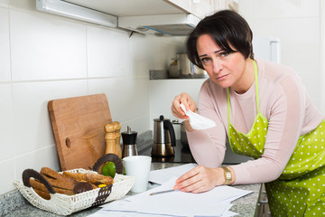 Frustrated woman crying over banking papers