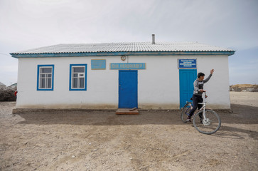 A boy rides a bicycle in front of the old school and library building in the remote part o the village of Karateren, near the Aral Sea, south-western Kazakhstan