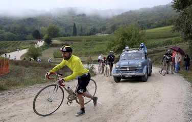 """Cyclist pushes his vintage bicycle on gravel roads during the Strade Bianche section of the """"Eroica"""" cycling race for old bikes in Gaiole in Chianti"""