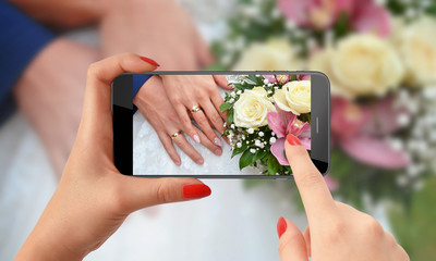Young woman taking photo with phone of brides and grooms hands with rings on flower bouquet