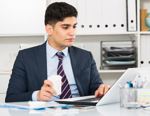 Male is working at a computer and drinking coffee
