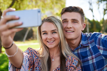 Cute couple taking selfie together in park