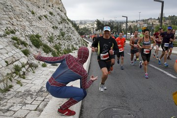 A man, dressed in a costume, encourages athletes running outside the Old City during the sixth international Jerusalem Marathon