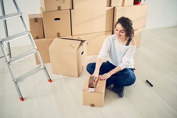 Caucasian girl taping boxes for moving in new apartment