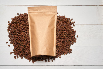 Mock-up craft paper pouch bag top view over white wooden table lying at coffee beans