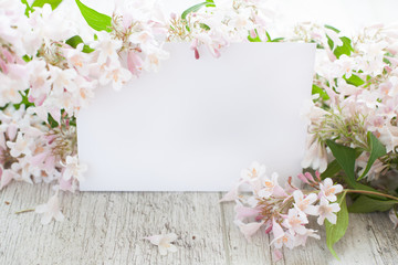 Mockup- flowers, peonies on a wooden table, white card. Woman's desk.