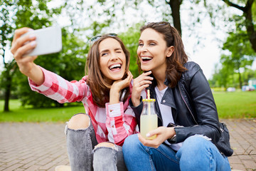 Cheerful young women siting together on longboard in park taking selfie