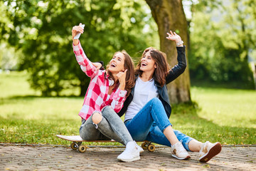 Cheerful young women siting on longboard in park posing for selfie photo