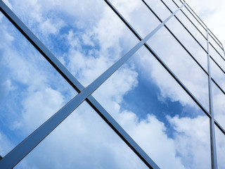 reflections of blue sky and clouds in glass facade of modern office building