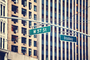 Vintage toned West 57 Street and Broadway hanging signs in Manhattan, New York City, USA.
