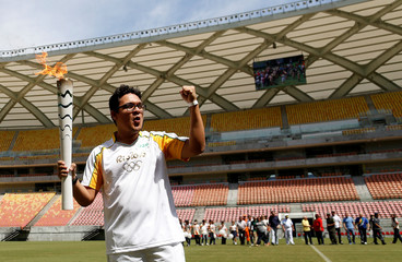 Brazilian designer Glauber Penha takes part in the Olympic Flame torch relay at the Arena da Amazonia stadium in Manaus