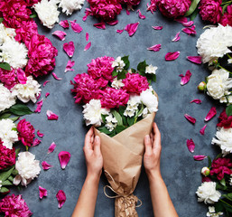 Top view of hands of young woman holding beautiful bouquet of peonies. Florist at work: pretty woman making summer bouquet of peonies on a working gray table. Flat lay composition.