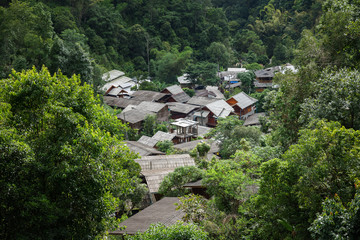 Scenery of rural village inside green area of tropical forest in Thailand.