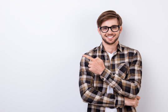 Smiling young nerdy bearded stylish student is standing on pure background in glasses and casual  outfit, pointing on the copyspace