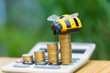 Growing coins and calculator on wood table with bee toy on green tree bokeh background.