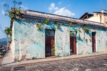 A street corner with one of the old ruined houses in Antigua, Guatemala with plants growing  over