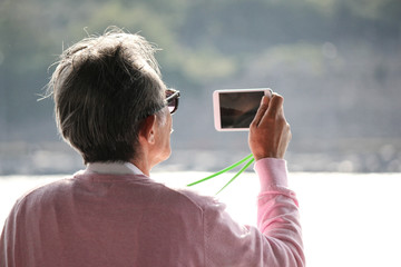 An grey-haired old man with glasses shooting the scene with his white smart phone
