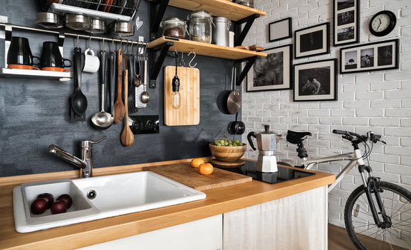 Design of modern home kitchen in the attic and rustic style. Black wall with shelves, trays, jars, mugs, sink. Against a wall with photos of a couple and a mountain bike.