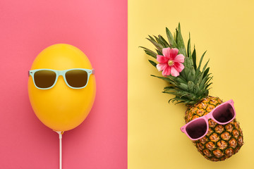 Fashion Pineapple and Yellow air Balloon. Bright Summer Color, Accessories. Tropical Hipster pineapple with Sunglasses. Creative Art concept. Minimal style. Summer party background. Fun