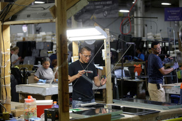 A worker looks over a glass window at Lippert Components in Goshen