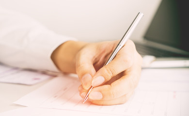 Business man's hand is signing on a document