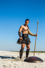 Spartan winner stands majestically with a spear and helmet in his hands