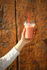 Fresh strawberries smoothie in female hand on wooden ancient background, healthy lifestyle