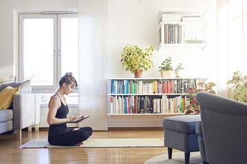 Girl doing yoga at home looking at tablet