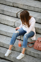 Woman sitting on stone steps, healthy lifestyle, with healthy snack, cup strawberries, smoothie, fresh, outdoor