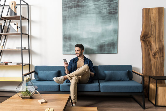 Happy youthful guy bearded resting with cellphone in living room