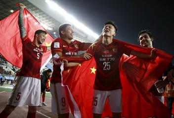 Zou Zheng of China's Guangzhou Evergrande holds Chinese national flag as he celebrates with teammates after winning their Club World Cup quarter-final soccer match against Mexico's Club America during in Osaka, western Japan