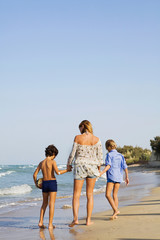 Woman walking with kids on beach