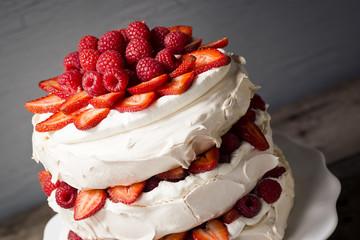 Layered Pavlova Cake with Meringue, Whipped Cream, and Fresh Strawberries and Raspberries
