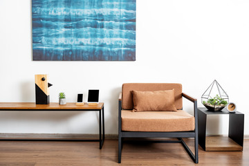 Table with comfy chair and bright picture in shiny apartment