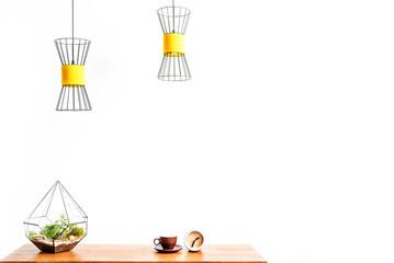 Hot beverage mug with watch and plant vase on desktop