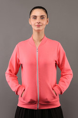 Young hipster girl wearing blank pink cotton zip up sweatshirt with copy space for your design or logo, mock-up of ltemplate womens hoodie, grey wall in the background