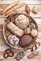 A basket full of delicious fresh bread on wooden background