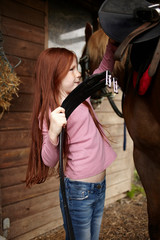 Girl fastening horse's saddle at barn