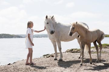 Girl petting horses on sandy beach