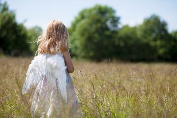 Girl wearing angel wings in field