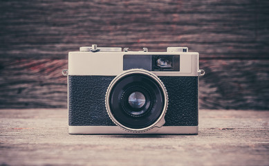 Retro film photo camera on wooden background.