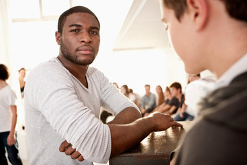 Group of friends at house party, young man looking at camera
