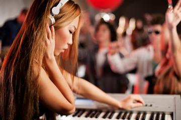 Young woman playing keyboard in nightclub