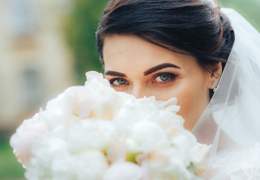 A beautiful warrior bride with blue eyes looks at the camera hiding behind a bouquet of white flowers